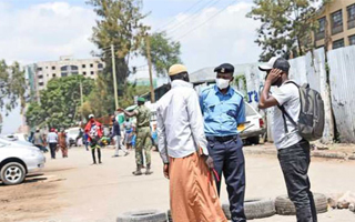 An officer talks to two men yesterday at a roadlock on Juja Road, which leads to Eastleigh. The area is in lockdown to curb the spread of Covid-19. PHOTO   EVANS HABIL   NATION MEDIA GROUP